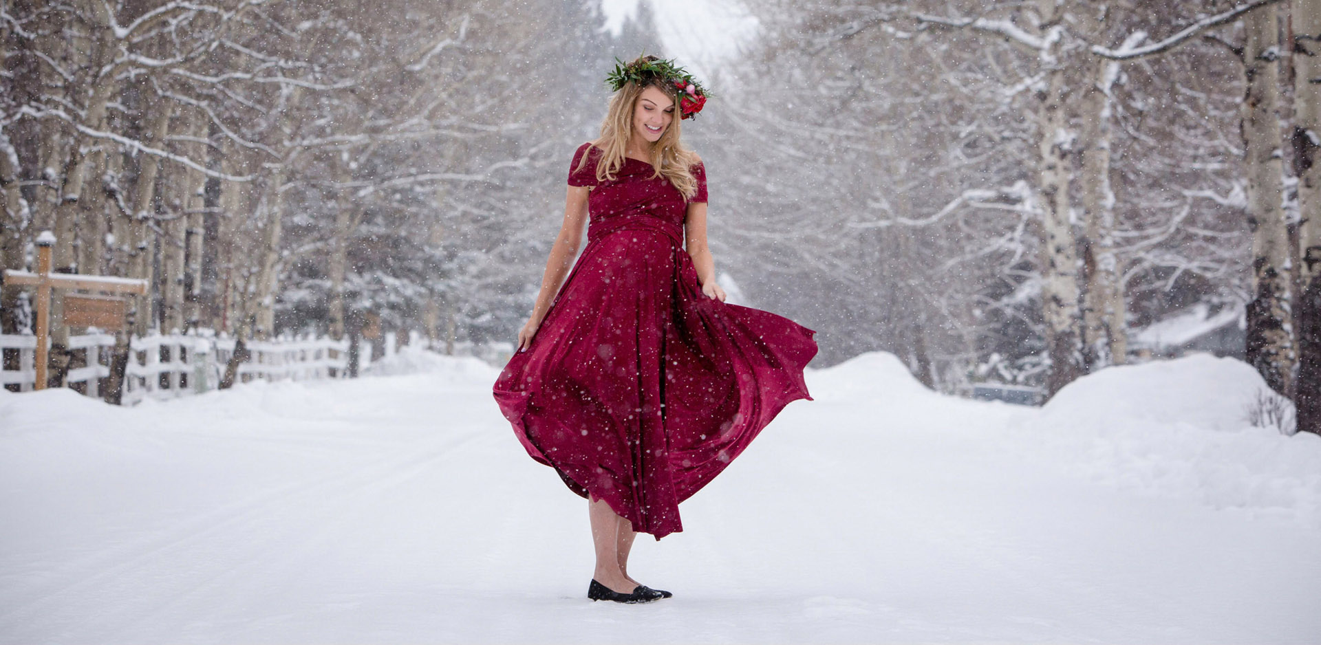 Maternity photo of woman in red dress spinning in snow