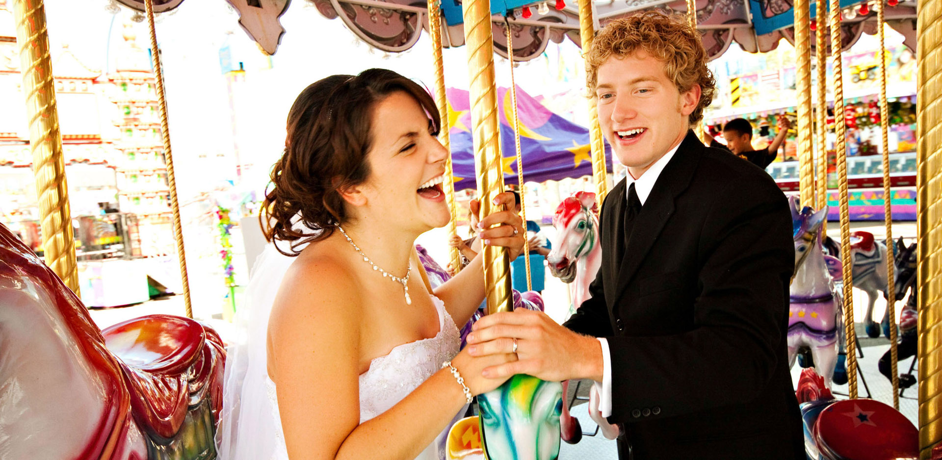 Bride and groom laughing on carousel during Whoop Up Days