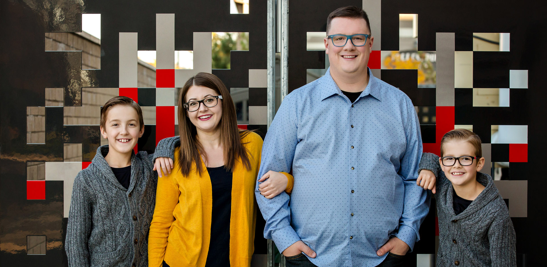 family standing in front of red pixel wall at Casa