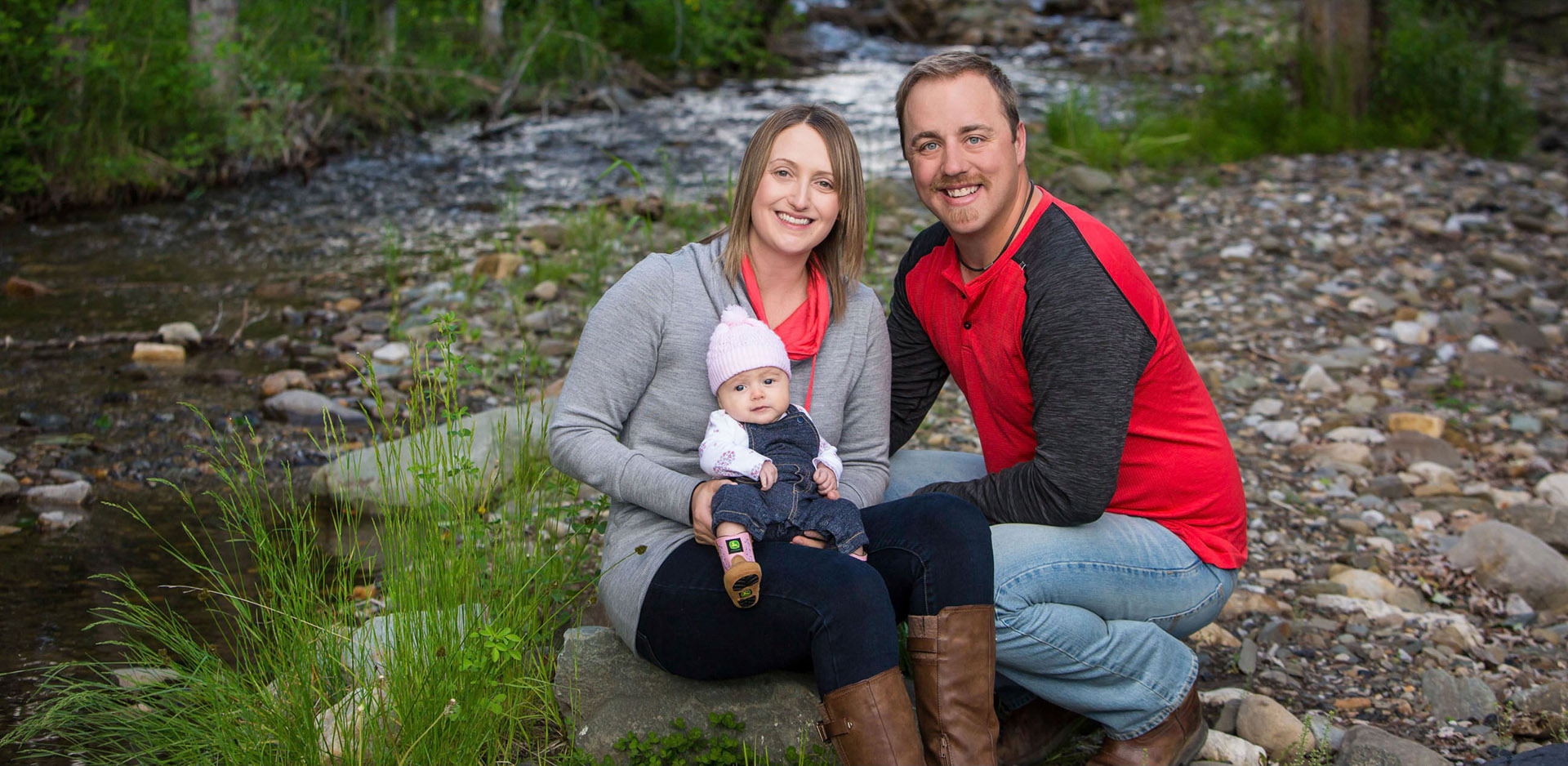 Family with baby sitting in front of creek in Hillcrest Alberta