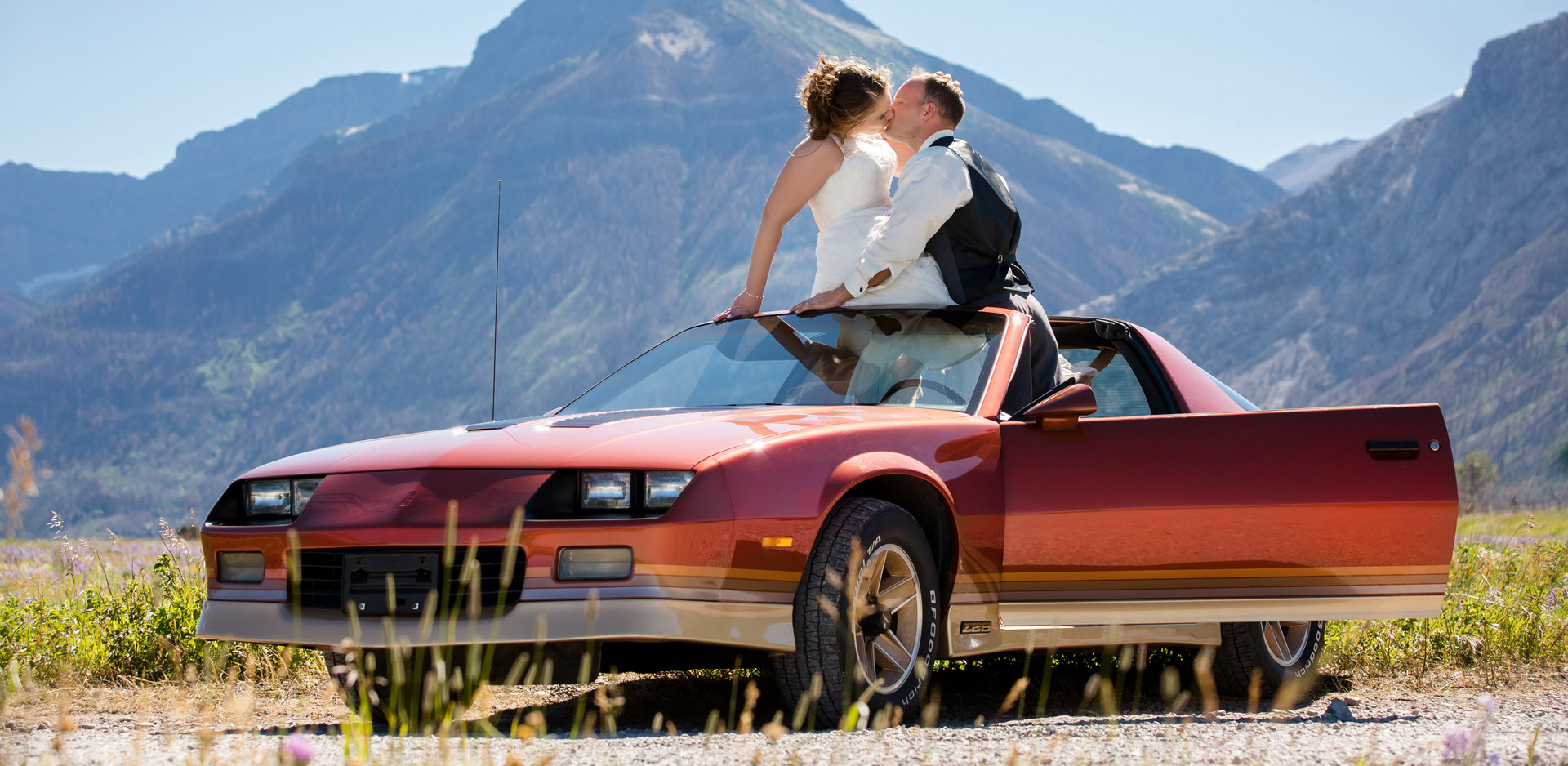 Bride and groom kissing on red vintage car in Waterton