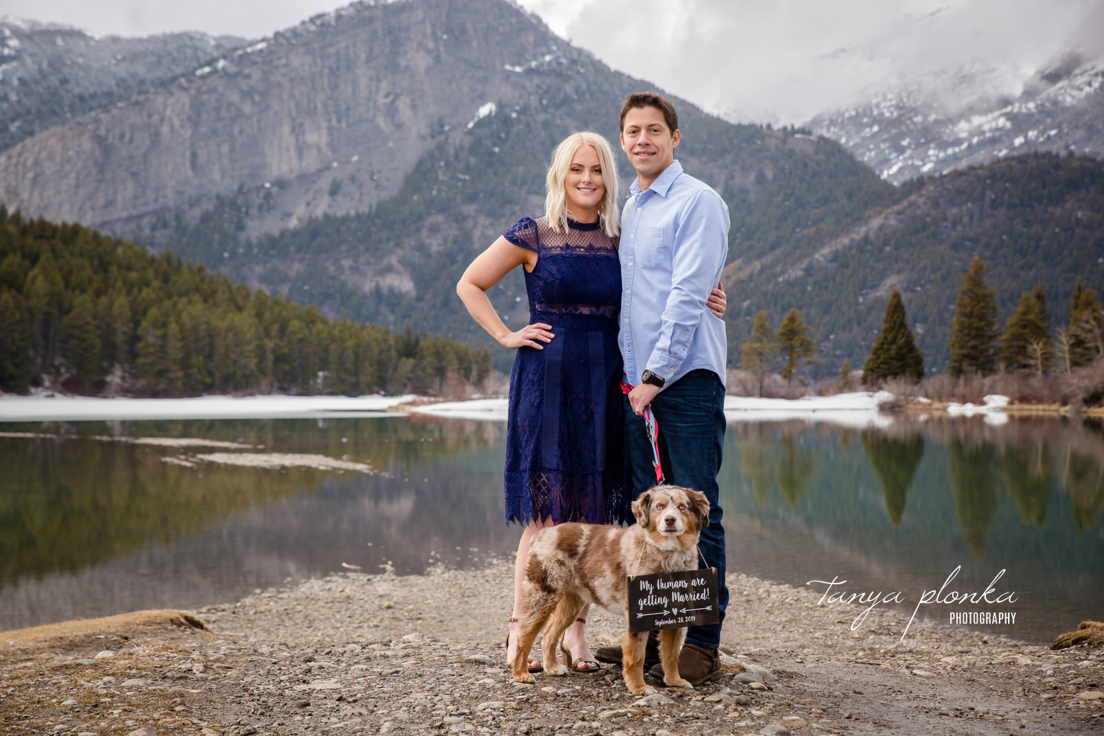 couple stand in front of Crowsnest Lake and mountains with dog wearing wedding announcement sign