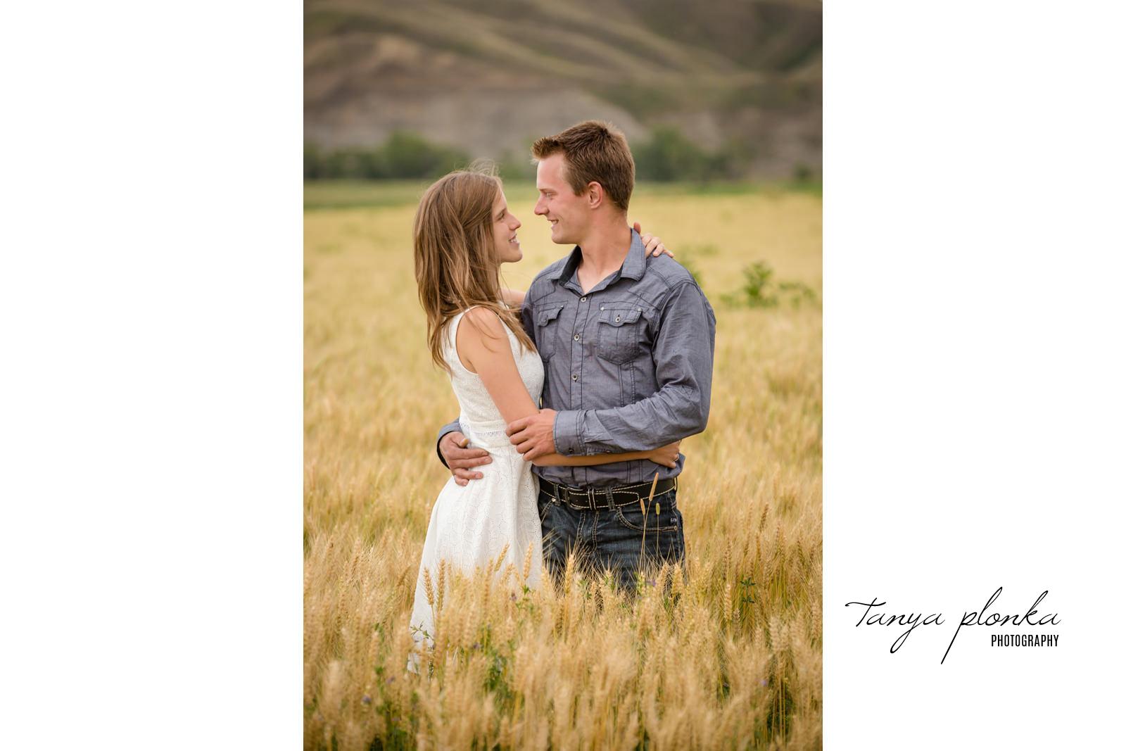 couple embrace in golden wheat field