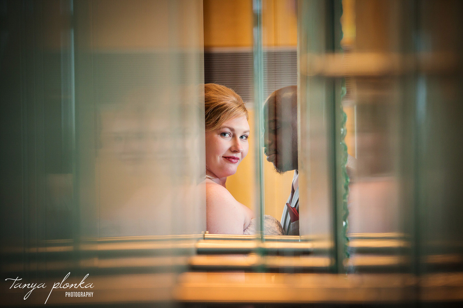 photo taken through layers of glass of bride and groom at Azuridge