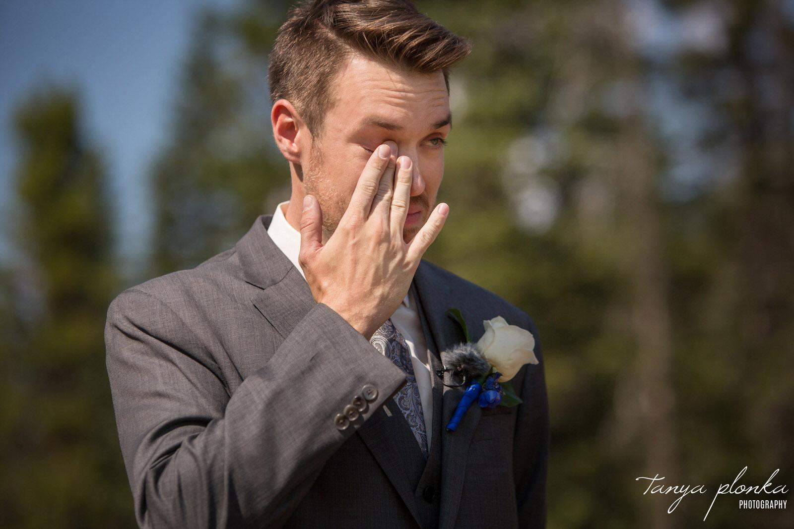 emotional groom wipes away tear at wedding ceremony in Banff