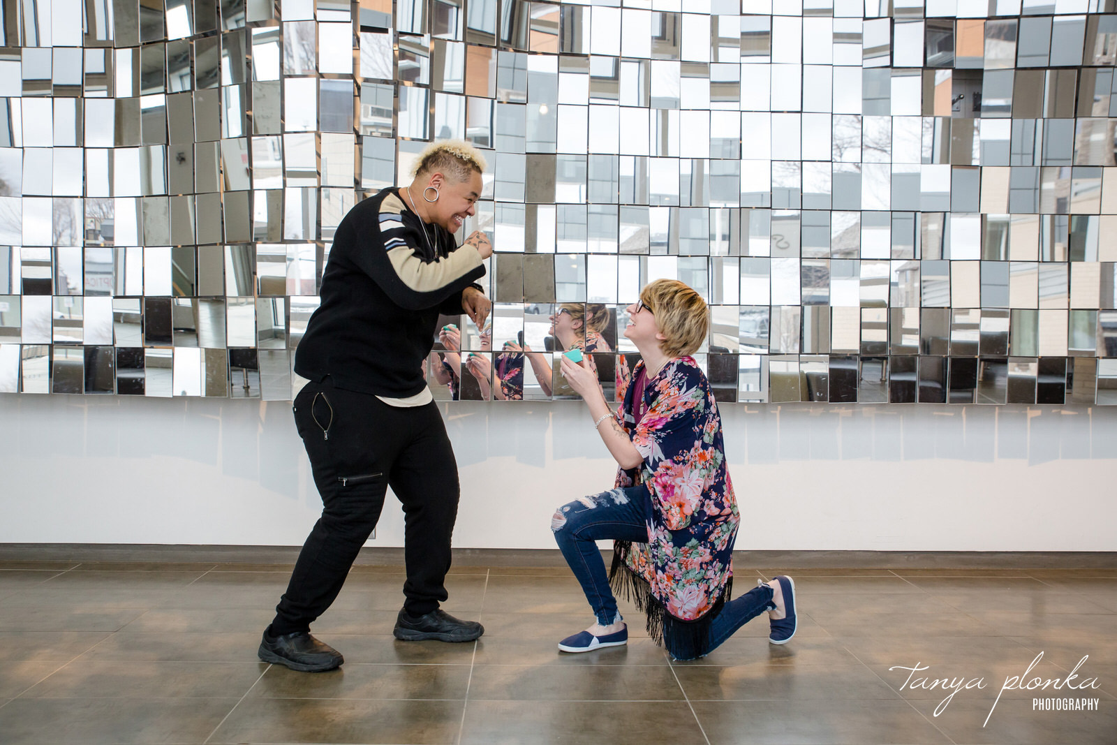 woman proposes to her girlfriend in front of mirror art installation at Casa in Lethbridge