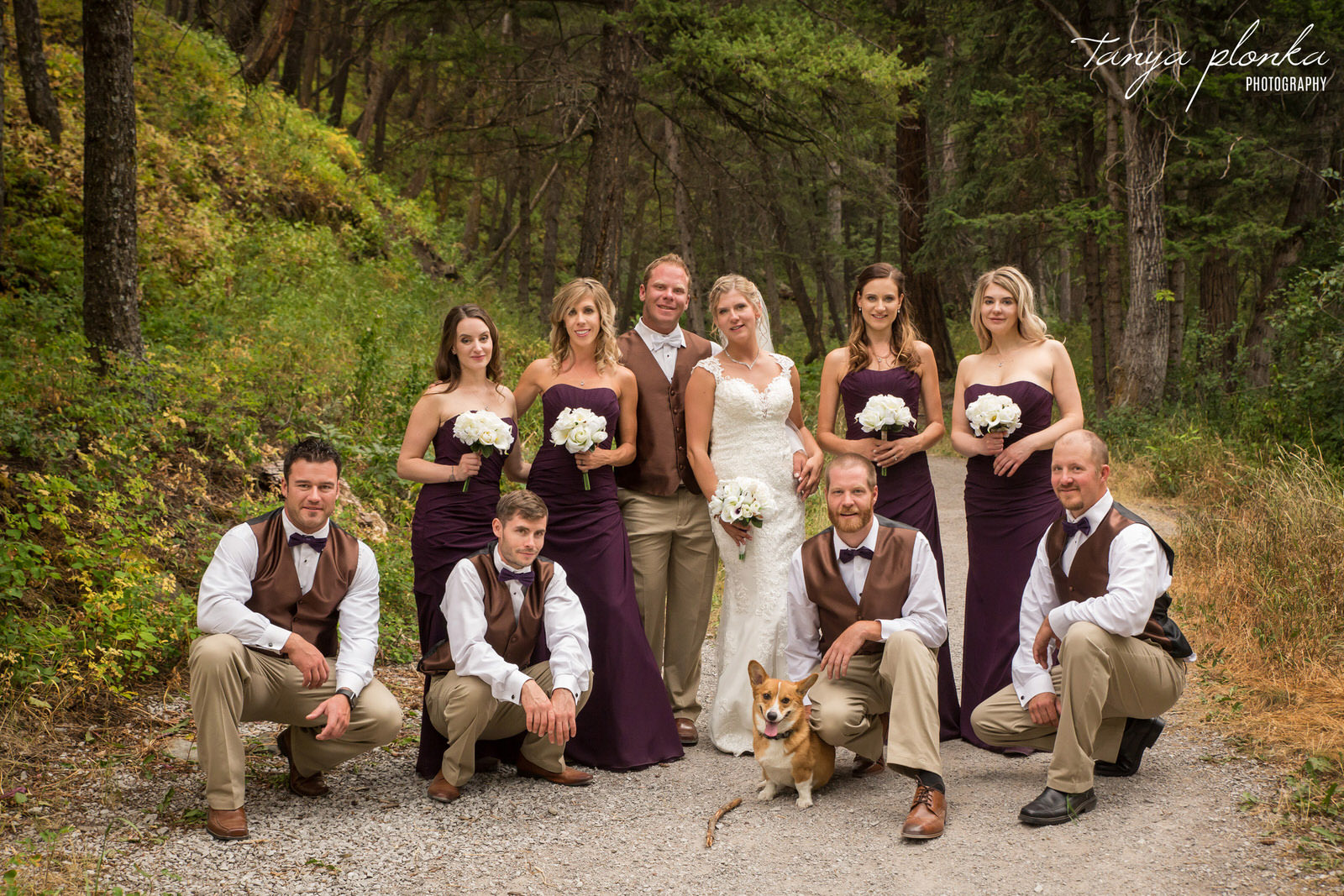 wedding party dressed in purple and brown stands in Miner's Path with smiling corgi in front
