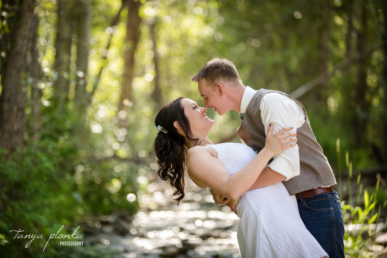 groom dips bride in front of out of focus stream in forest