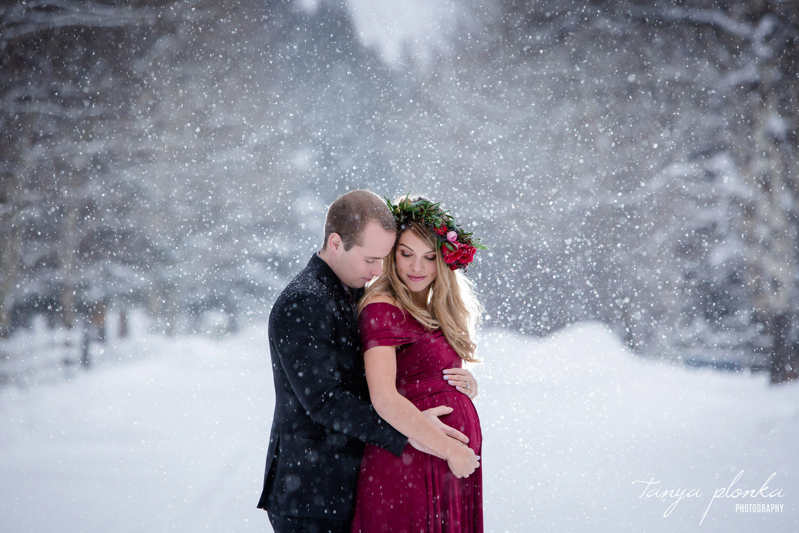 pregnant woman in red dress and husband in black suit embrace in falling snow