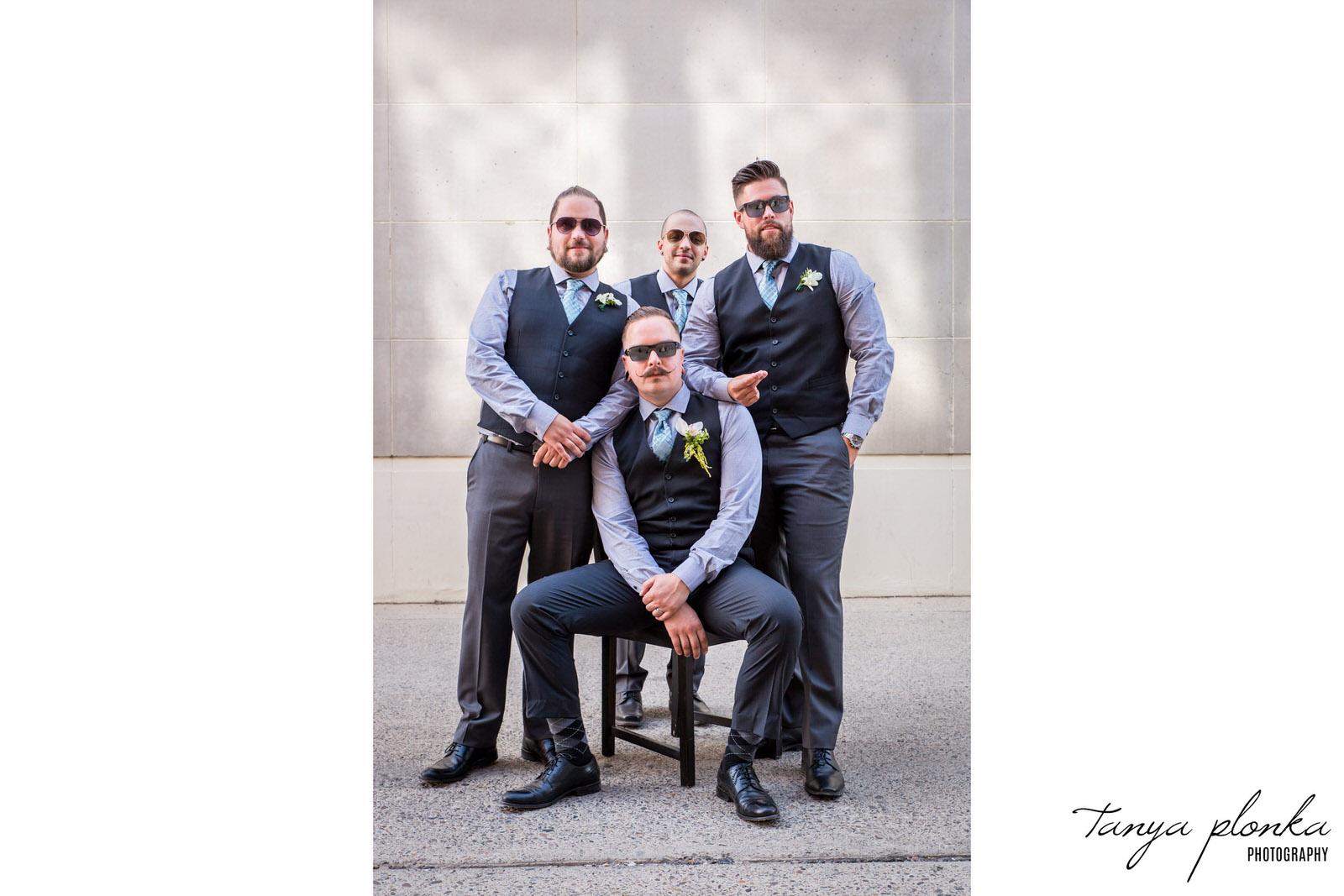 groomsmen pose around groom sitting on chair in alley