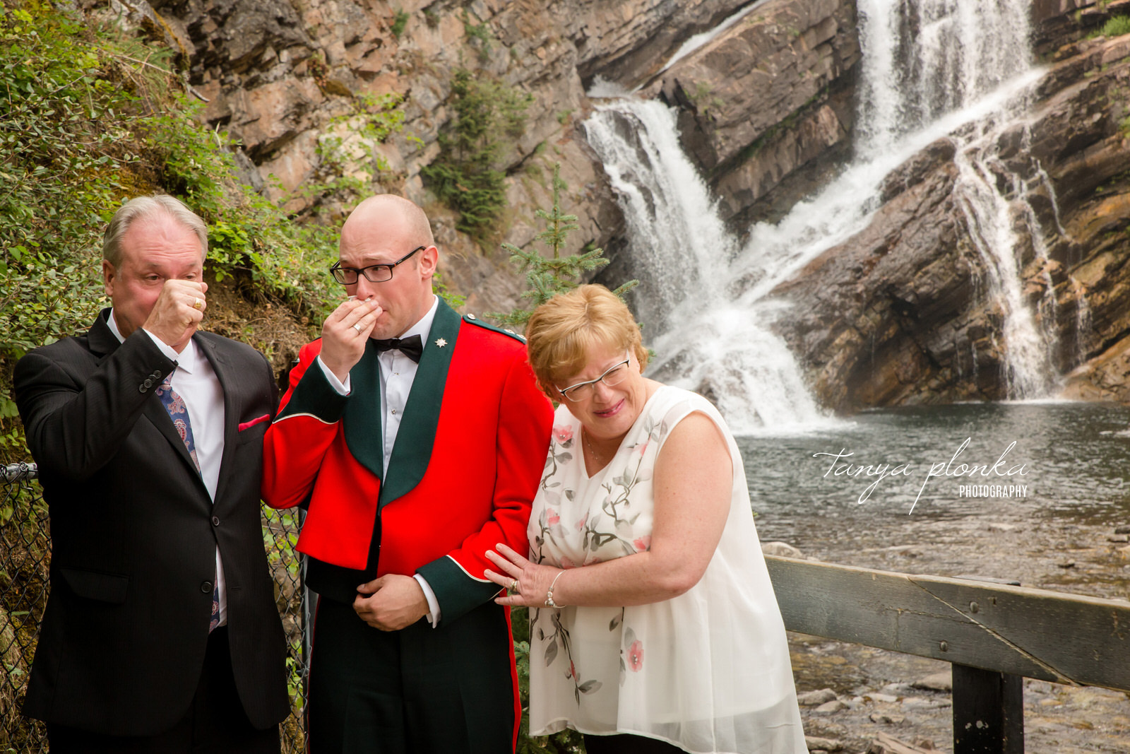 Groom in military suit and parents cry while standing in front of waterfall