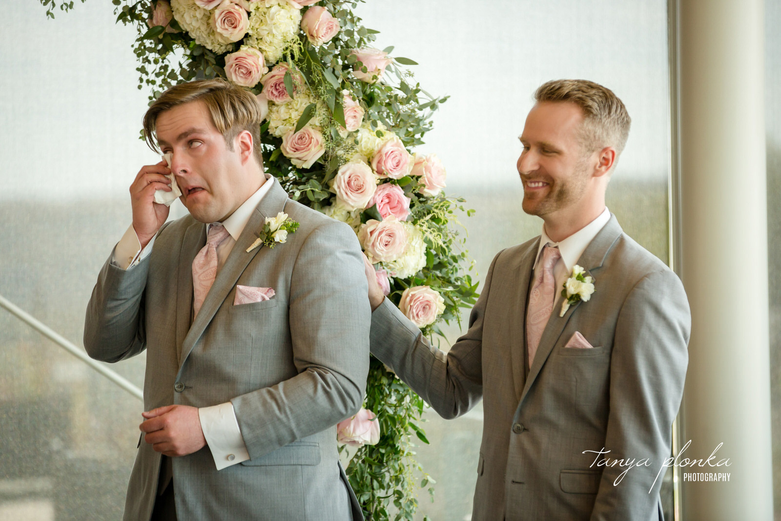 groomsman in gray suit wipes tear with tissue while other groomsman laughs and puts arm on shoulder