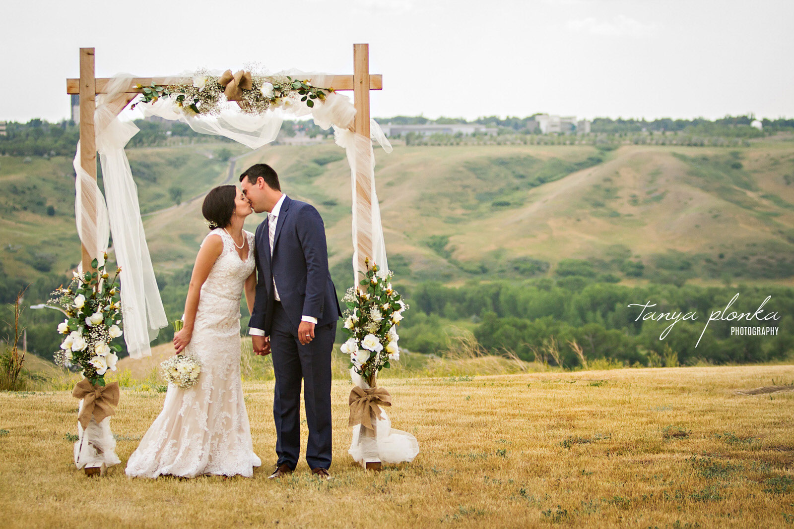 bride and groom kiss while standing under archway at edge of Lethbridge coulees