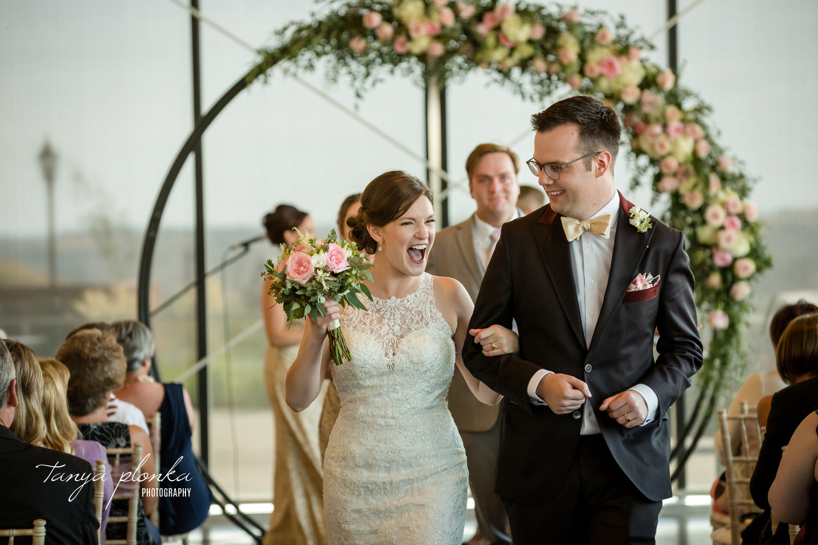 bride and groom laugh while walking down the aisle at the Galt Museum