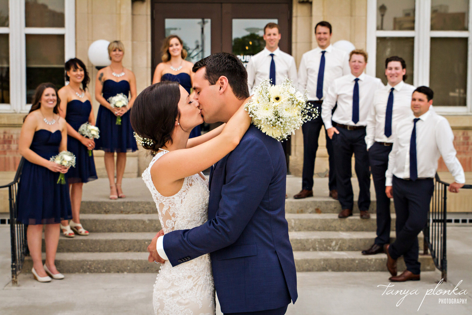 bride and groom kiss while their wedding party stands behind them on the stairs at the Galt Museum