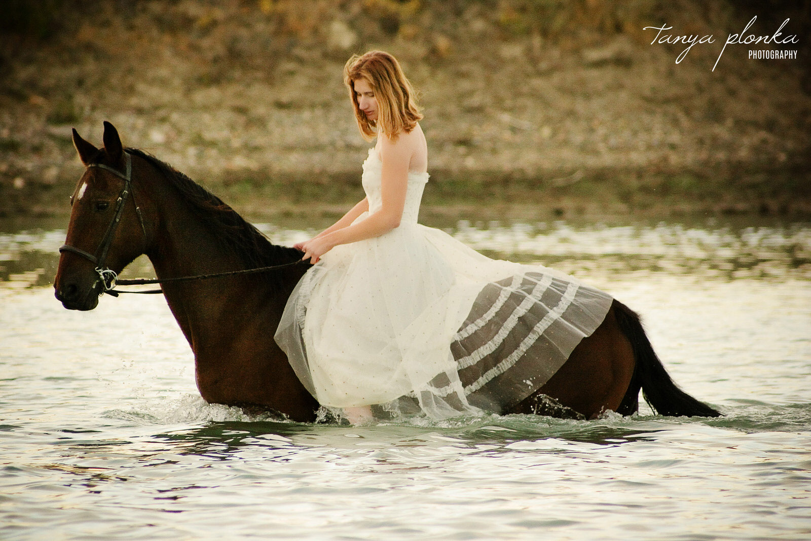 woman in white dress rides brown horse through the river