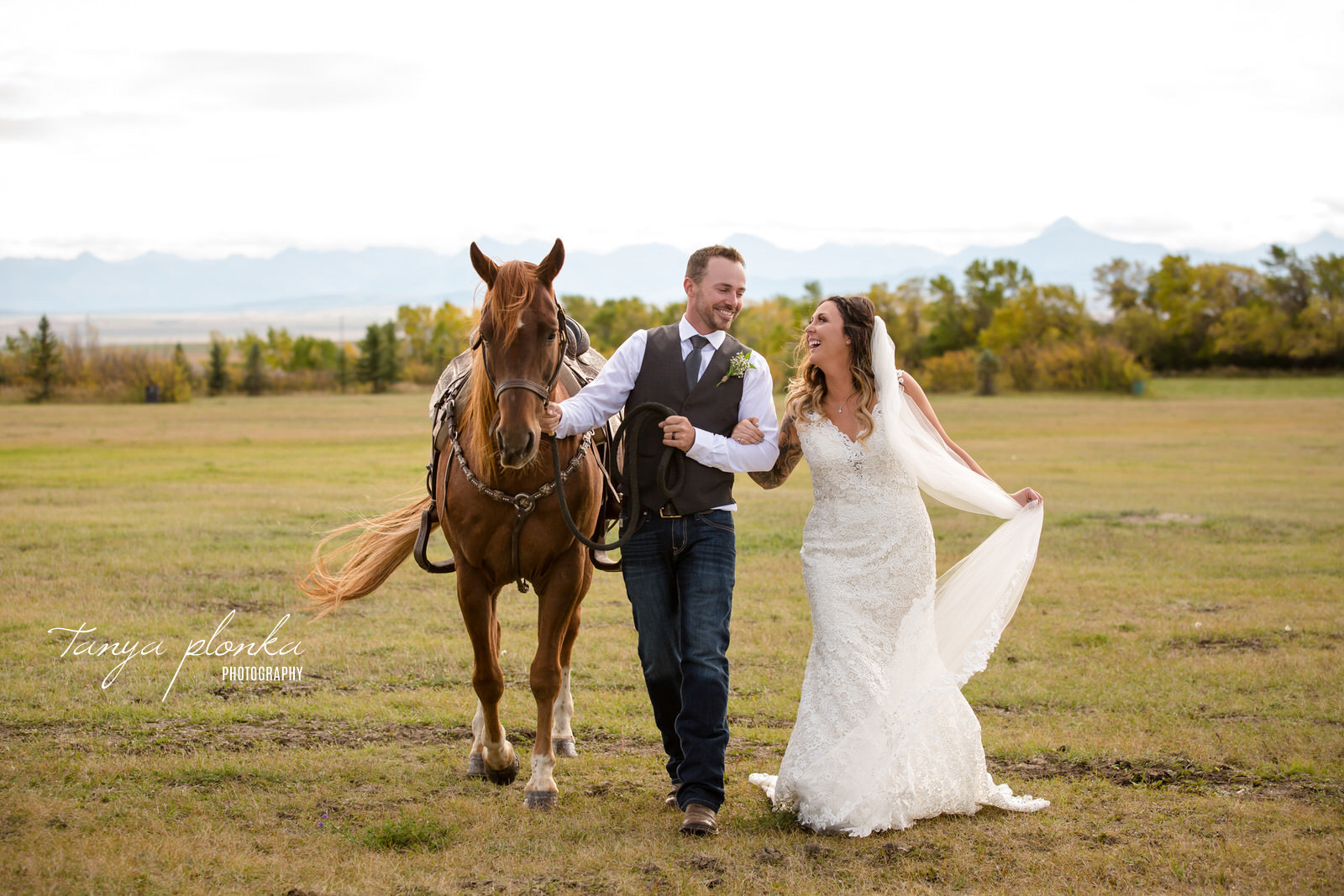 bride and groom laugh at each other while leading brown horse