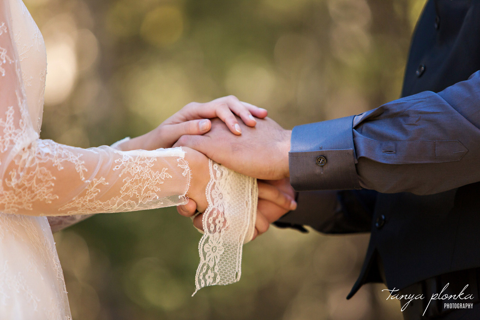 closeup of bride and groom hands wrapped in lace during hand fasting ceremony at Gladstone Mountain Ranch