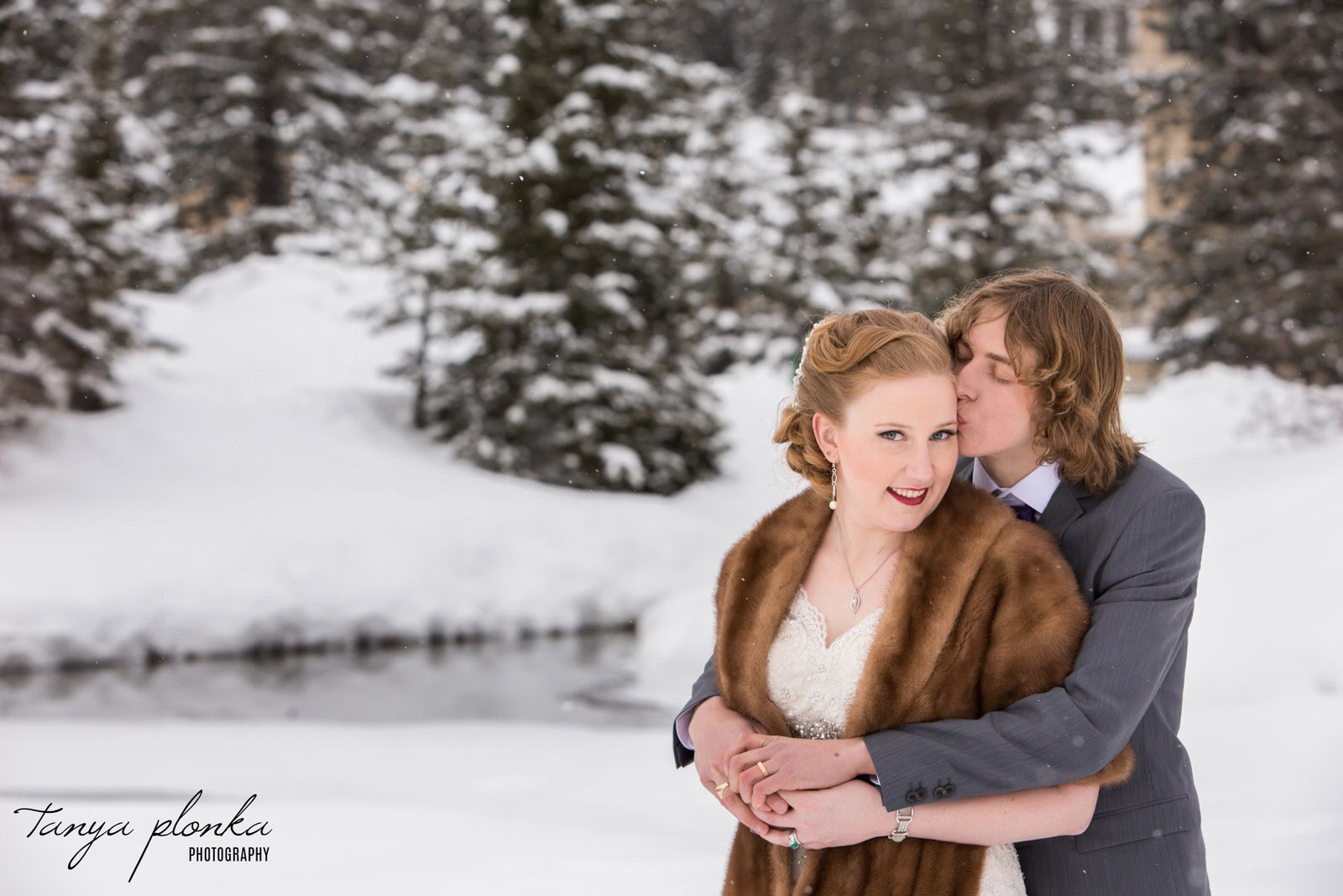 groom kissing bride on cheek at snowy Lake Louise winter wedding