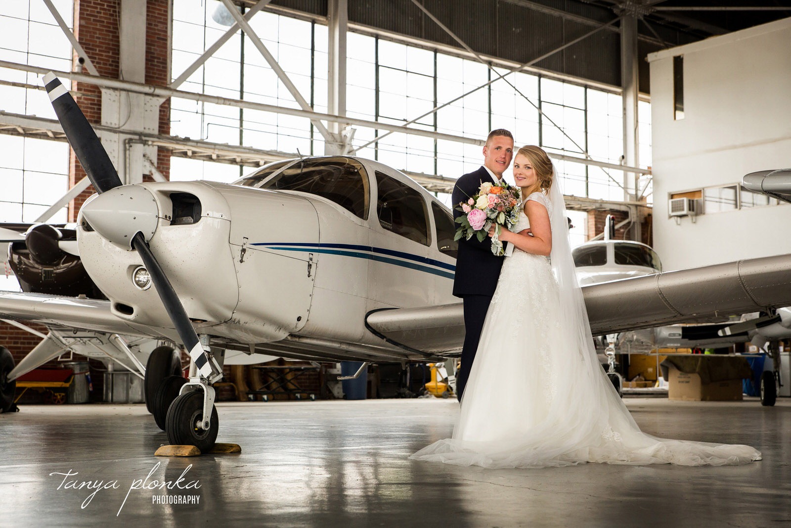 bride and groom pose in front of small airplane in airport hangar in Lethbridge