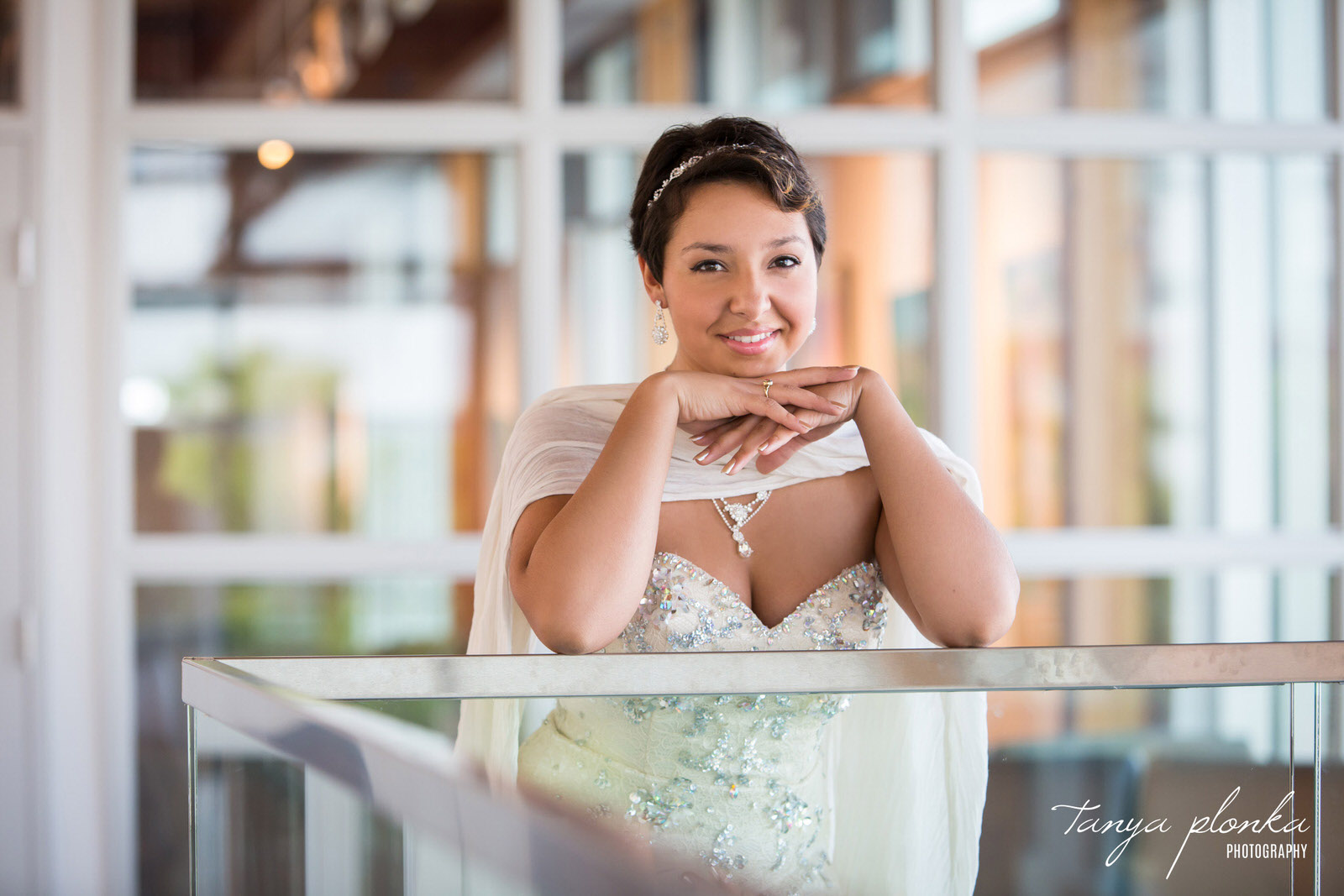 high school grad in sparkly white dress leans on railing inside the Casa art gallery