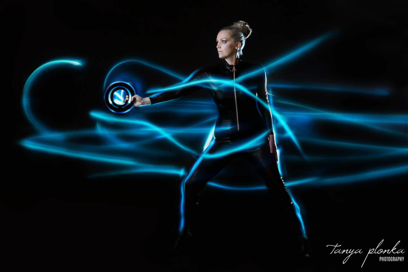 blonde woman in black bodysuit holding Tron identity disc poses against black background with blue light painting around her