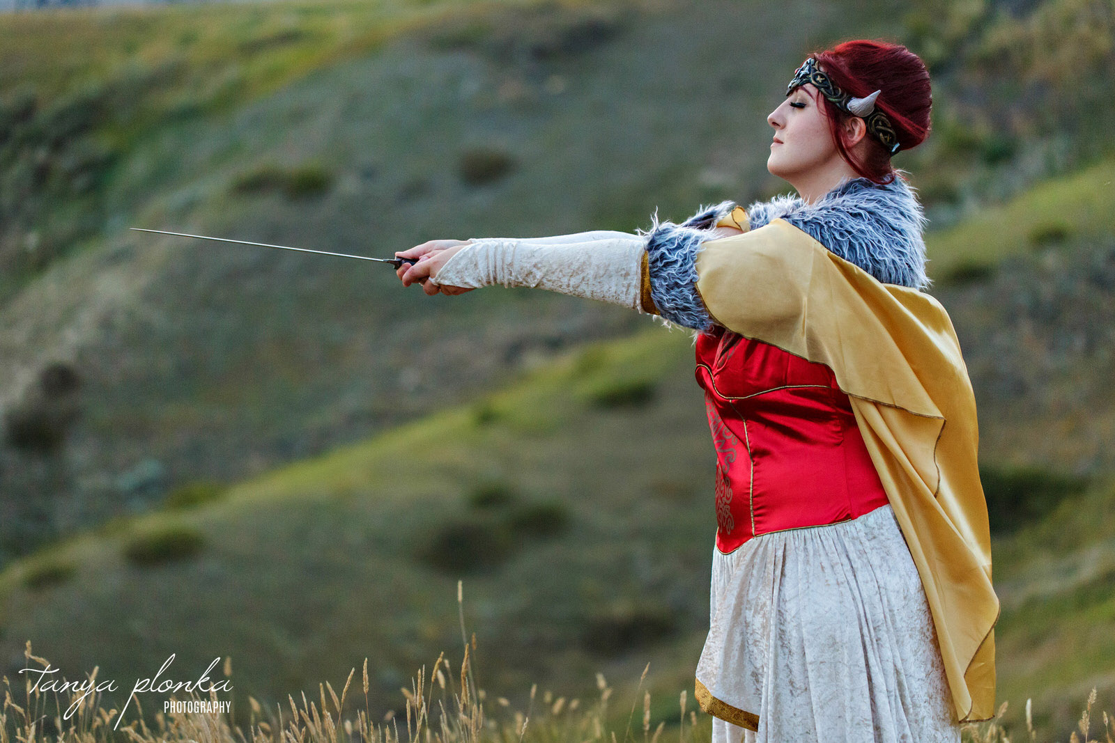 woman wearing viking cosplay holds a sword in the Lethbridge coulees