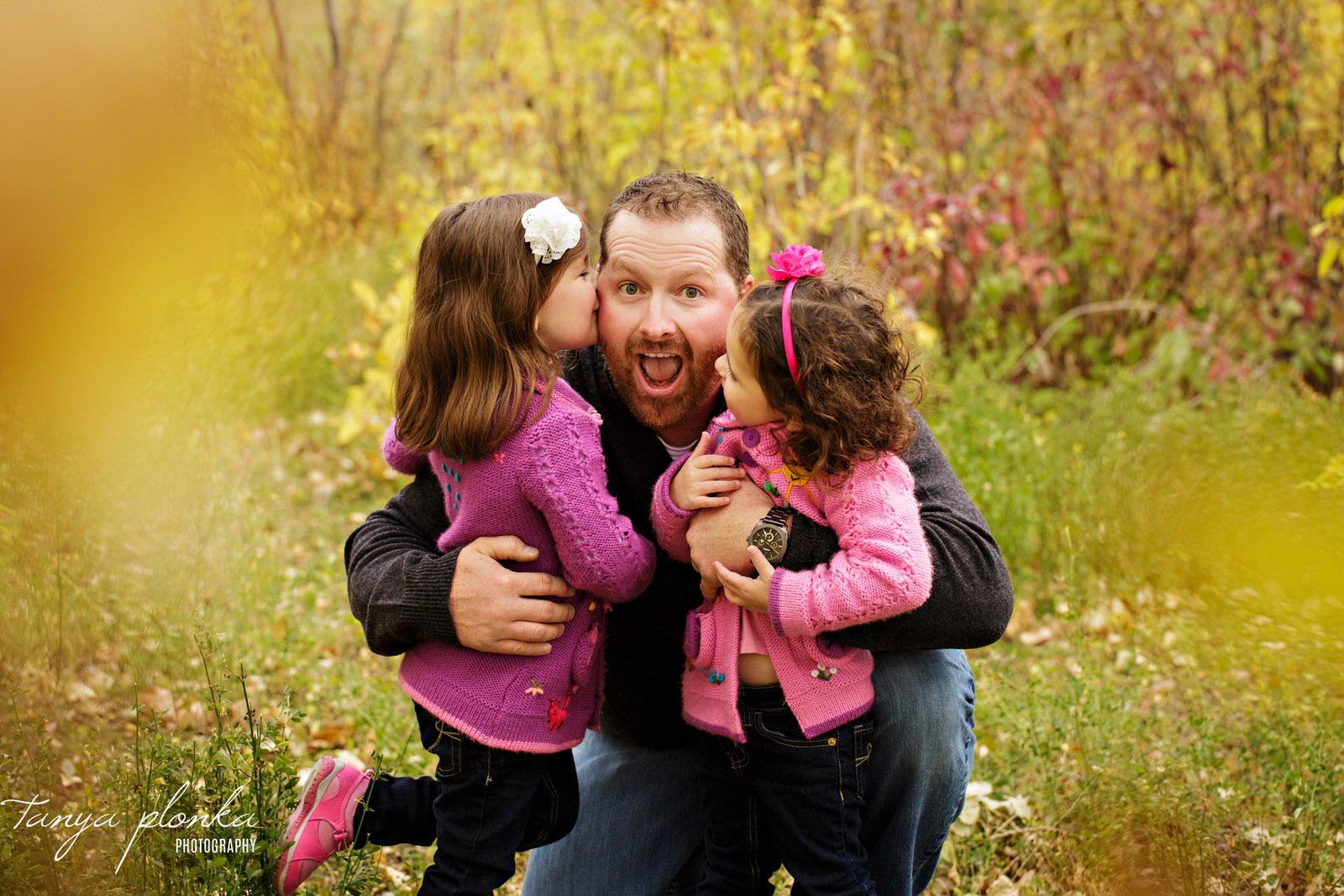 two sisters give their dad a kiss on the cheek