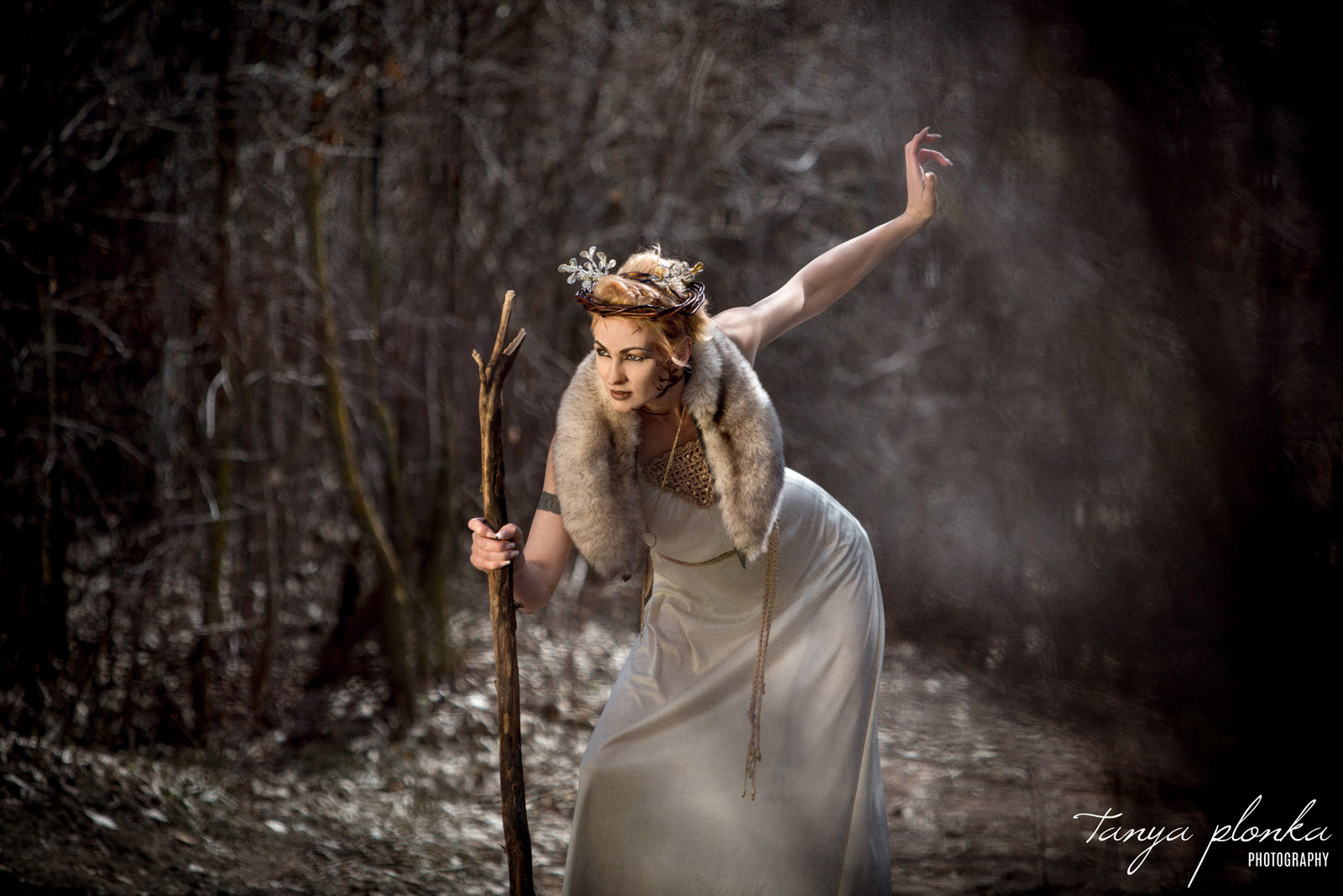 woman dressed in white poses with wood staff in dry winter woods