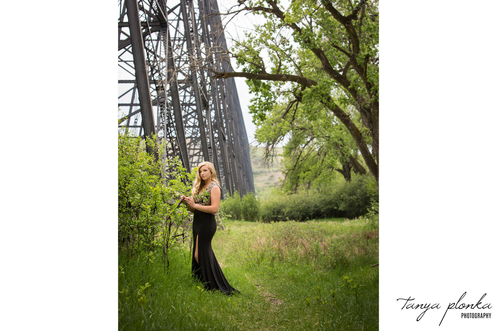 high school grad in black dress stands in front of the high level bridge in Lethbridge