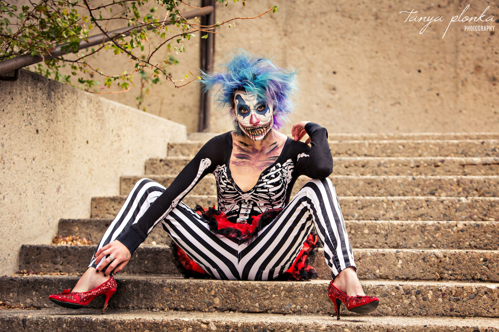 woman with creepy clown makeup and blue hair, wearing striped pants and red shoes, sits on stairs