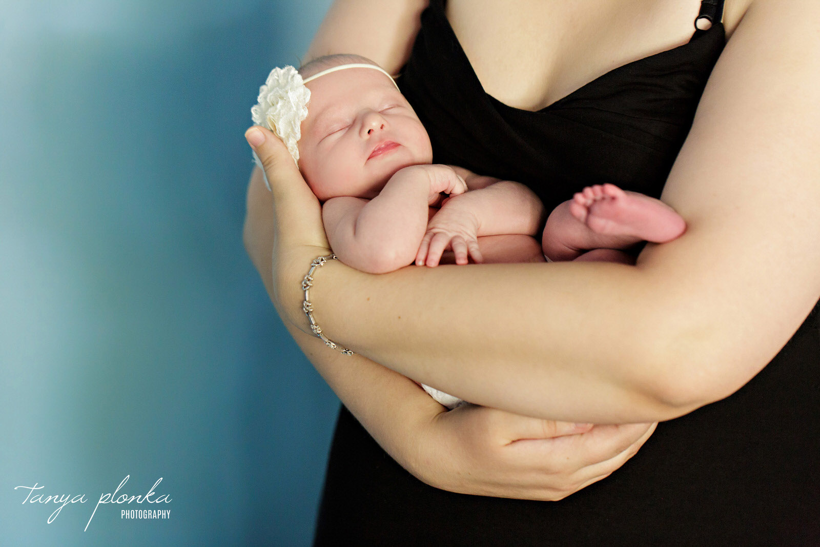 mother cradles newborn baby with aqua wall in background