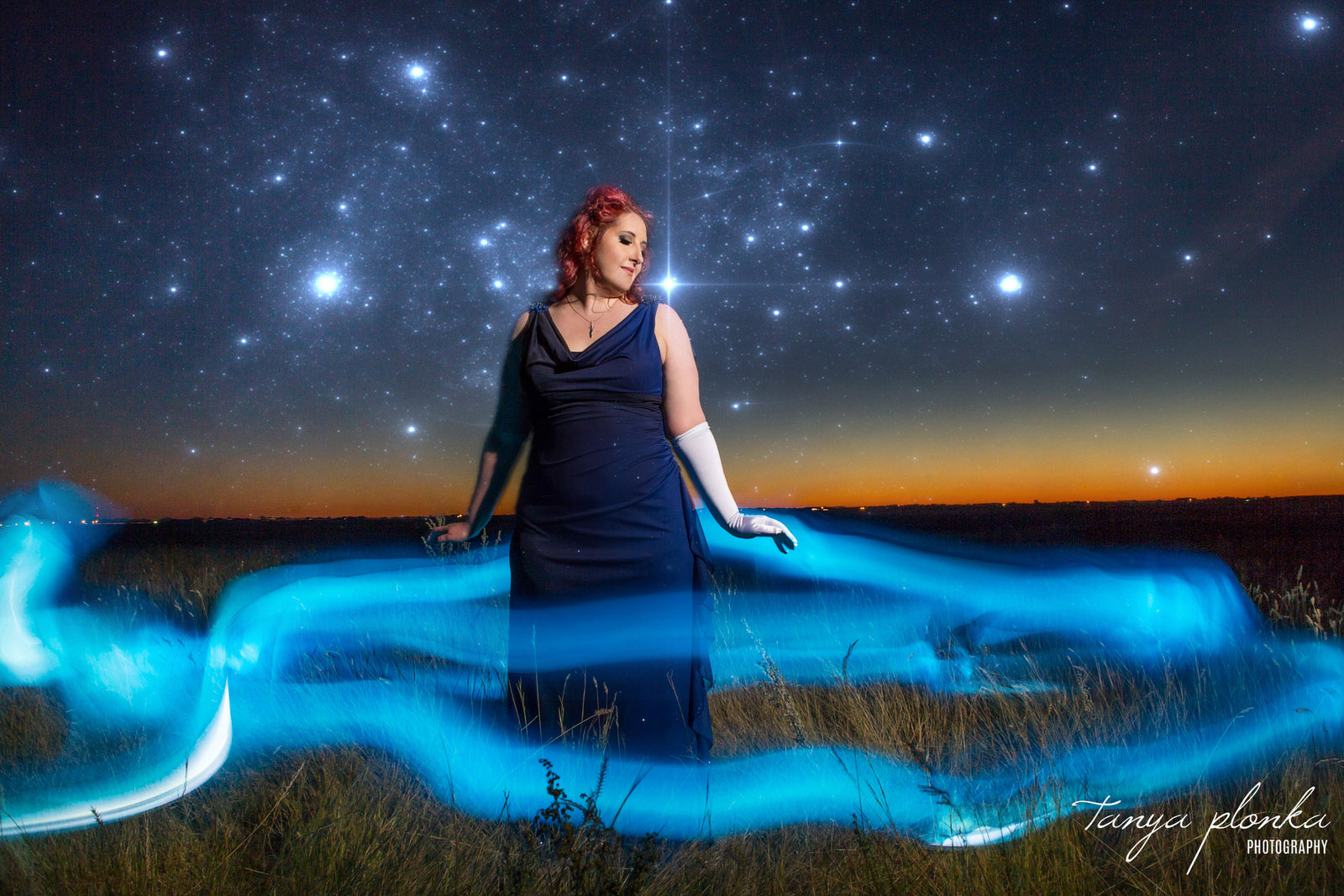 woman in blue dress stands with blue light swirling around her