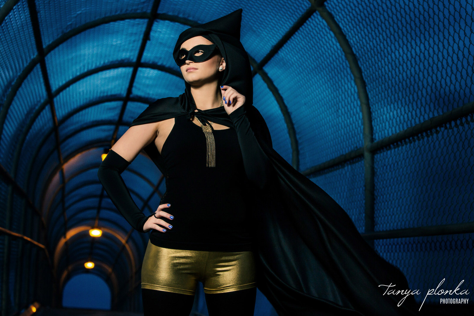 woman in gold and black super hero costume standing in Lethbridge highway overpass