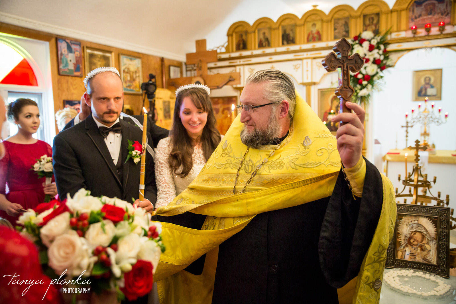 bride and groom follow Orthodox priest holding crucifix as they circle the alter