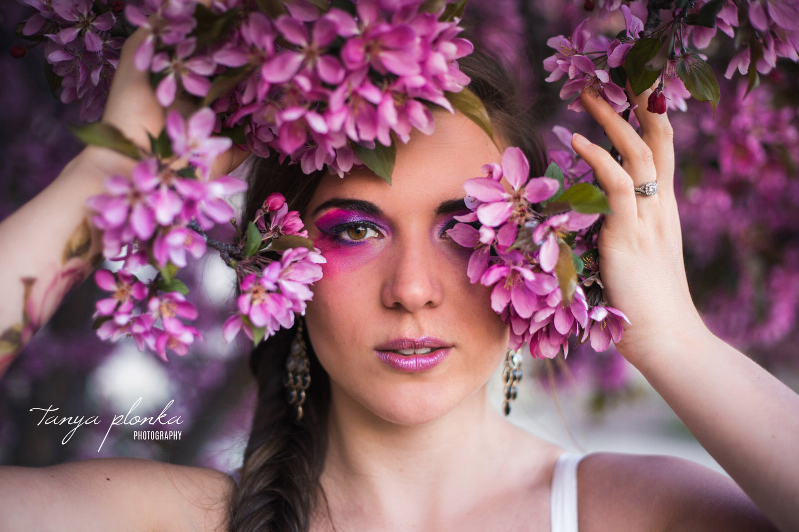 woman in pink eye shadow peeks out from pink flower blossoms