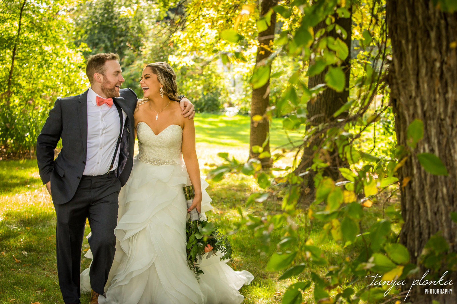laughing bride and groom walk through trees at Lethbridge Research Centre with arms around each other