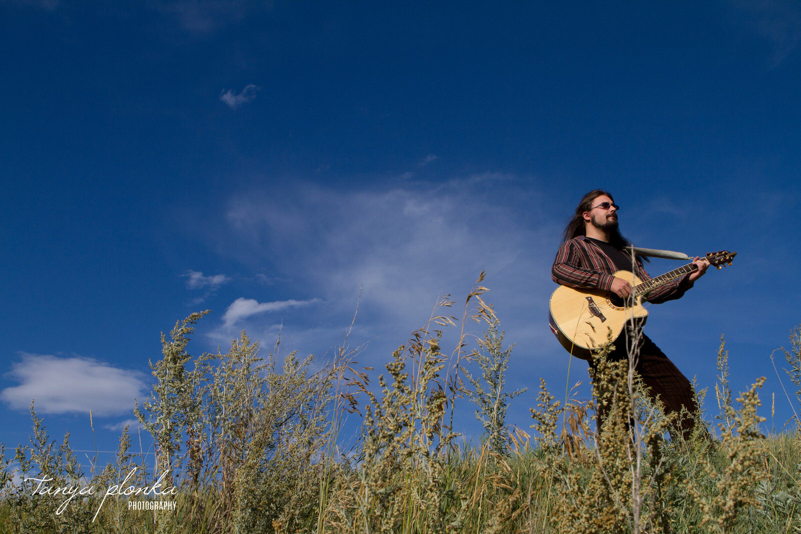 man playing acoustic guitar in front of bright blue sky