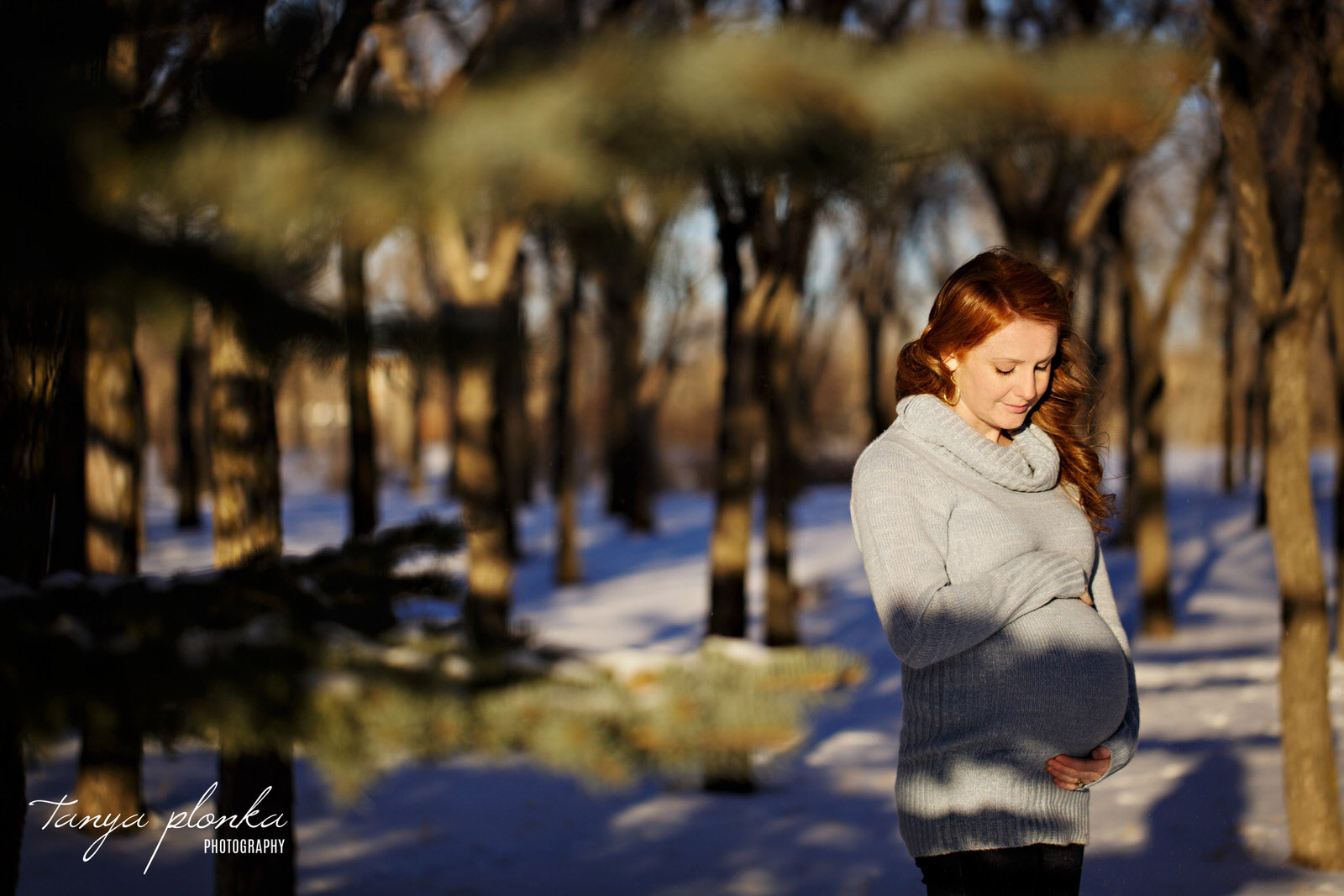 pregnant woman looks down at belly in snowy forest