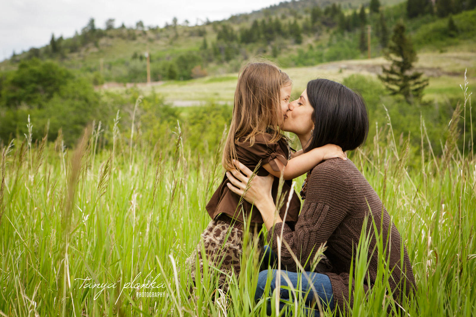 mother kissing young daughter in long green grass