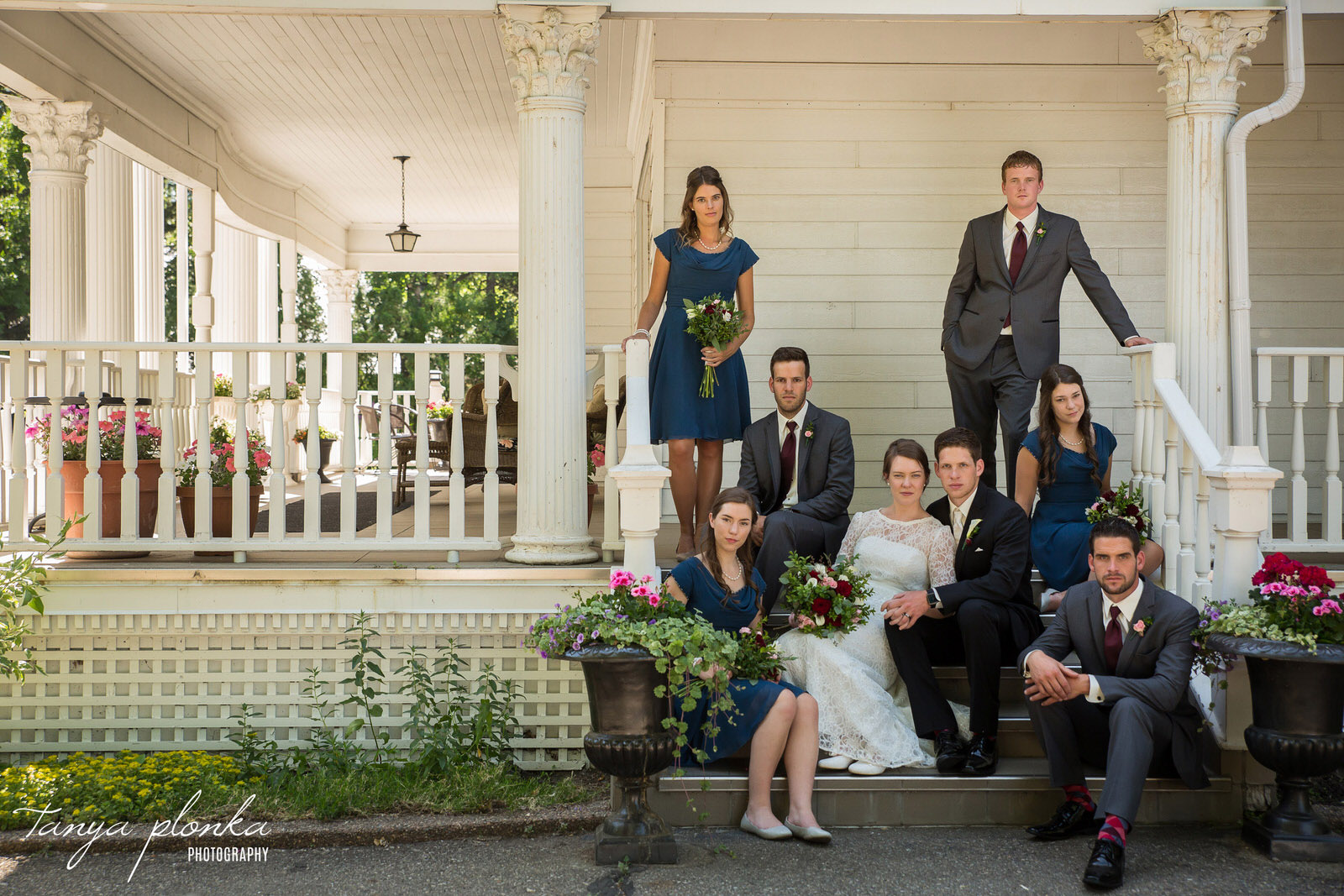 wedding party sit on stairs at the Norland Historic Estate