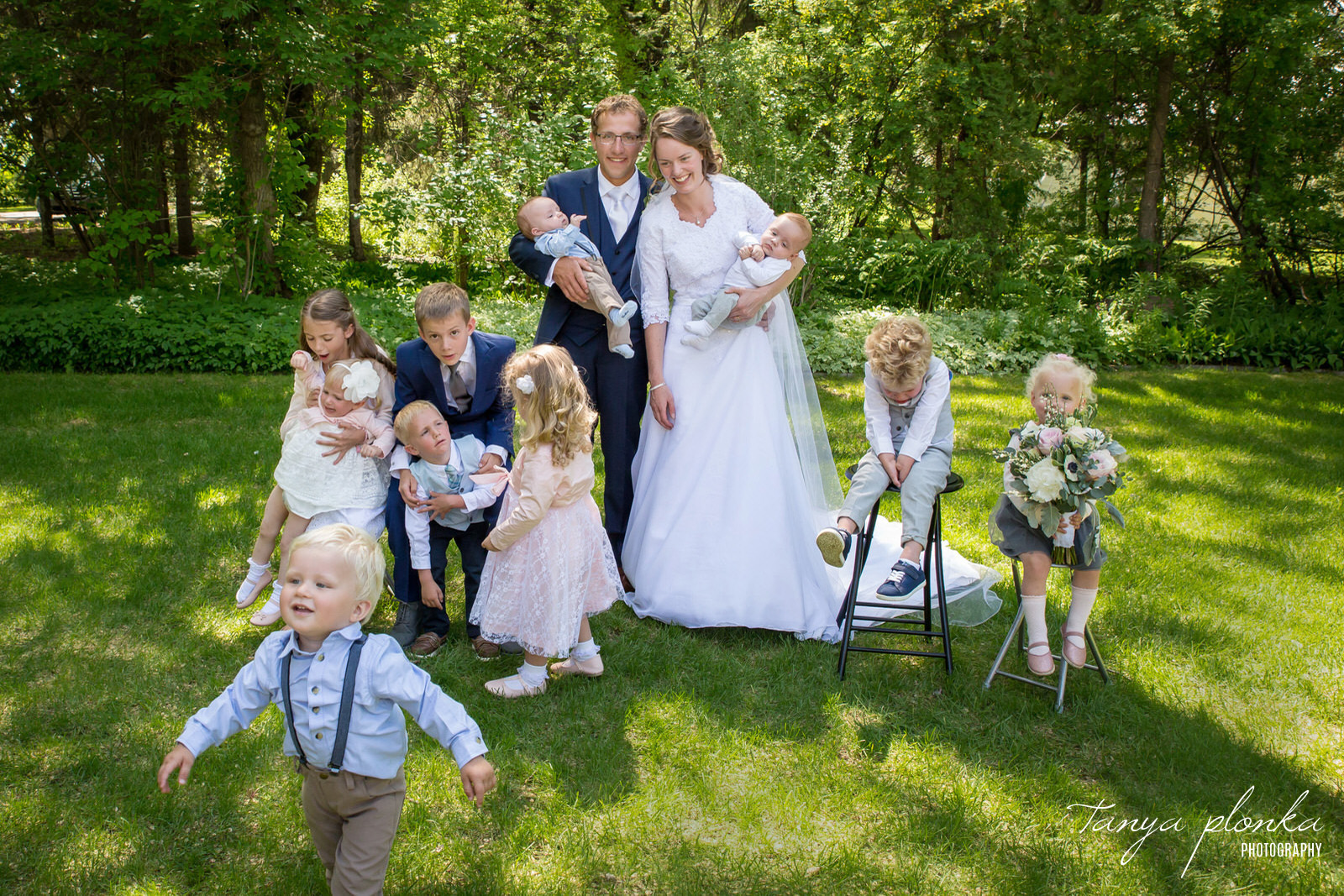 Bride and groom attempt to pose with nieces and nephews while the kids do not behave