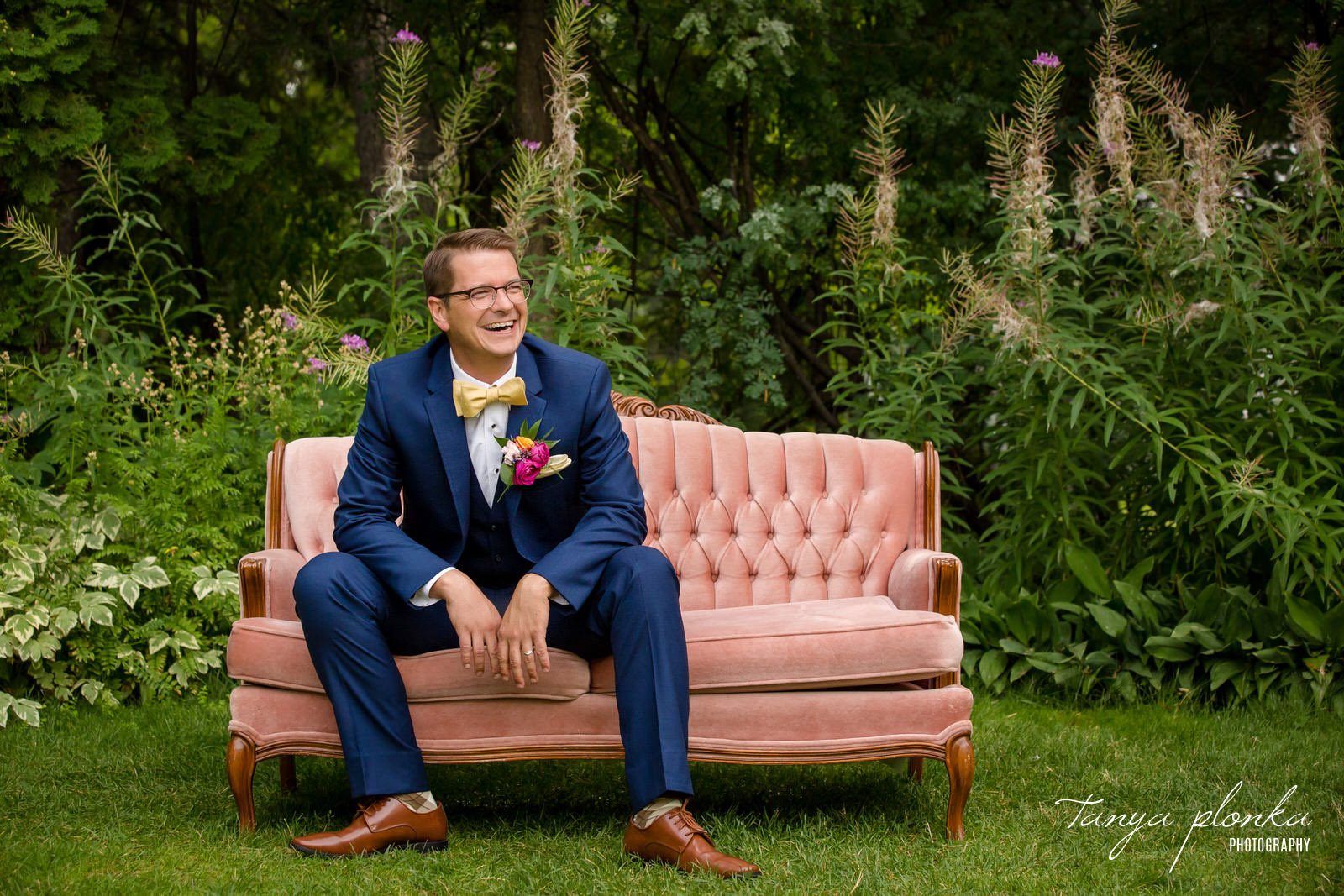 Groom in navy blue suit laughs while sitting on pink couch outside