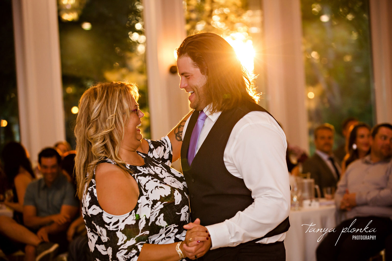 mother and son laugh while dancing together with sunlight behind them