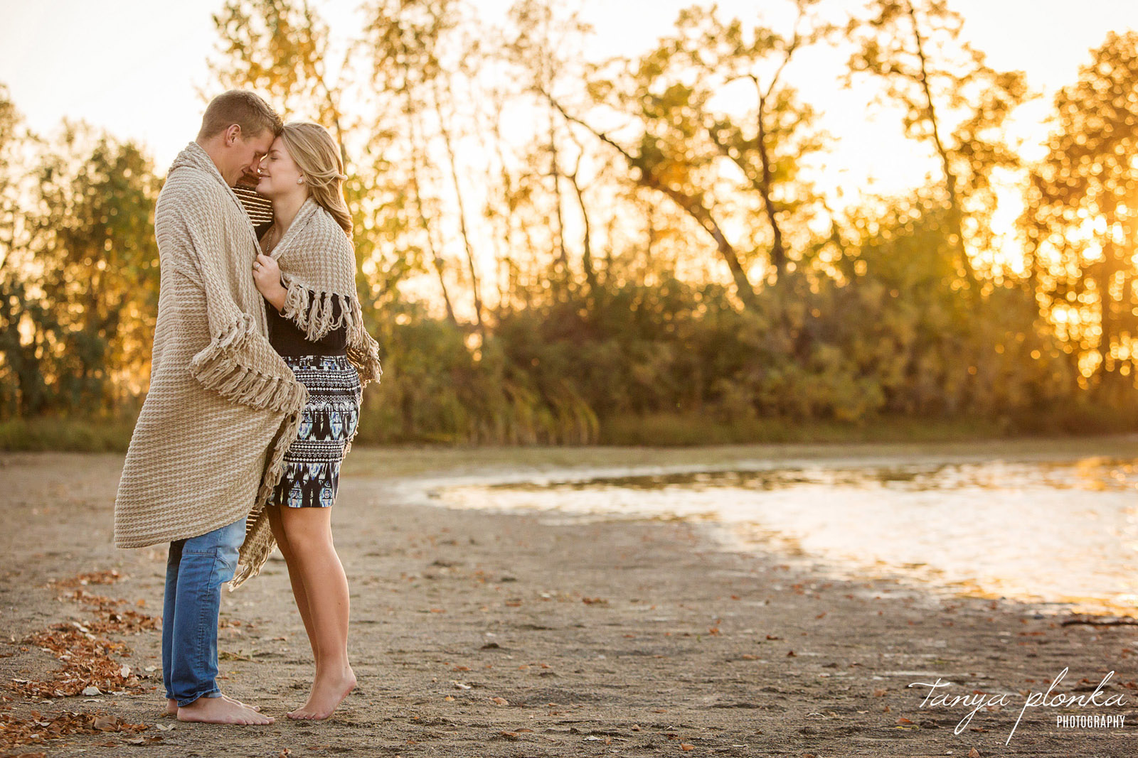 couple stand barefoot on beach at Park Lake during golden hour wrapped in blanket