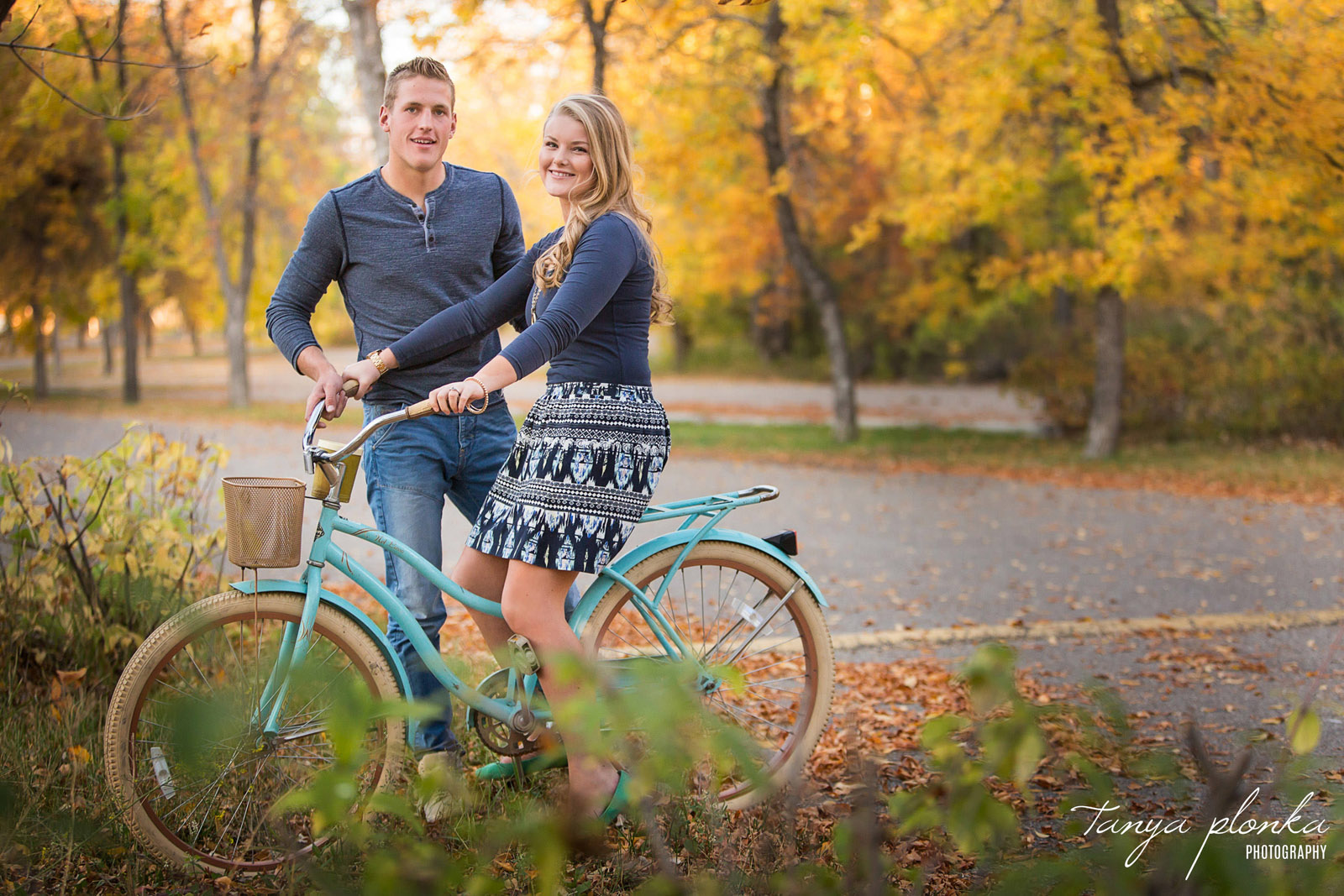 girl sits on vintage blue bicycle with boyfriend standing behind her at Park Lake in autumn