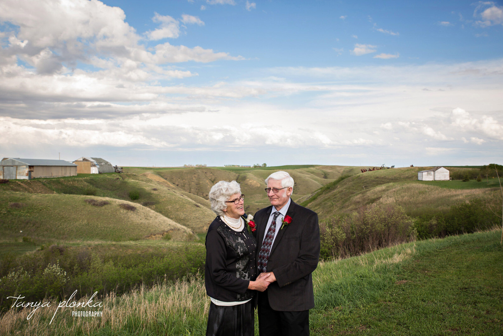 older couple hold hands at edge of green coulees at Coyote Flats in Picture Butte
