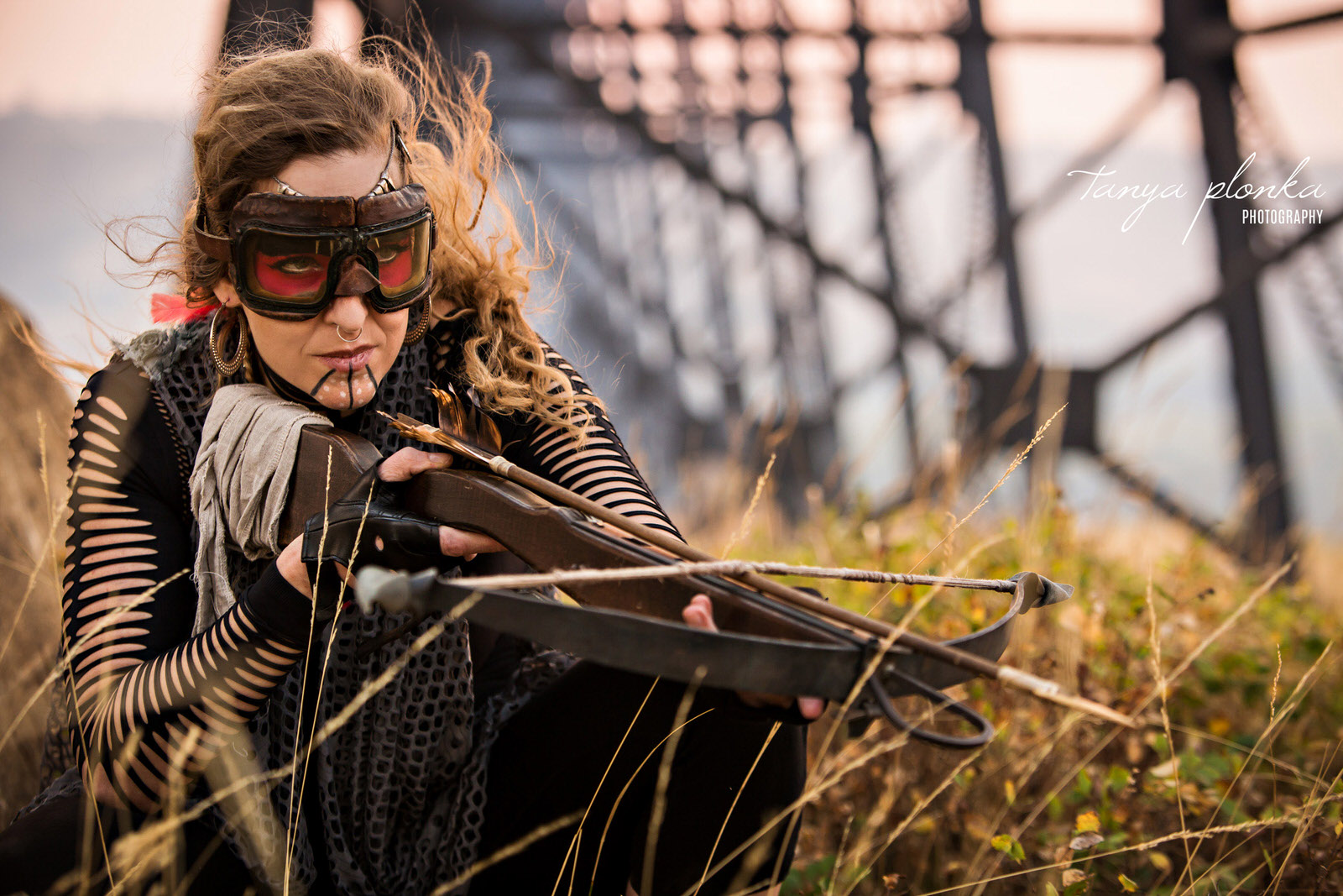 woman holds crossbow by the Lethbridge high level bridge in post apocalyptic cosplay