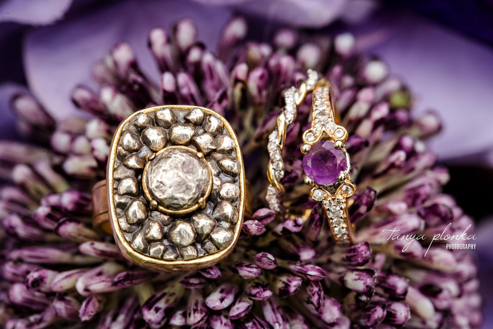 wedding rings sitting in purple bouquet flowers