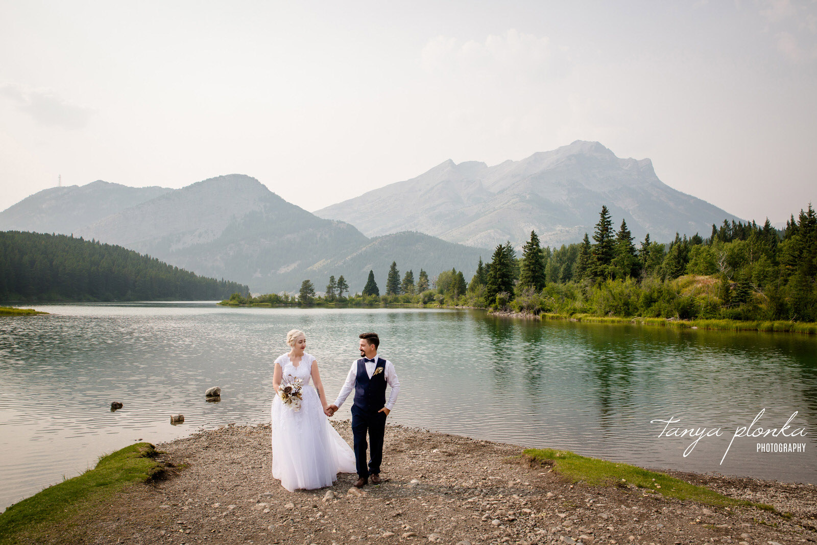 bride and groom walk side by side holding hand in the middle with Crowsnest Lake behind them